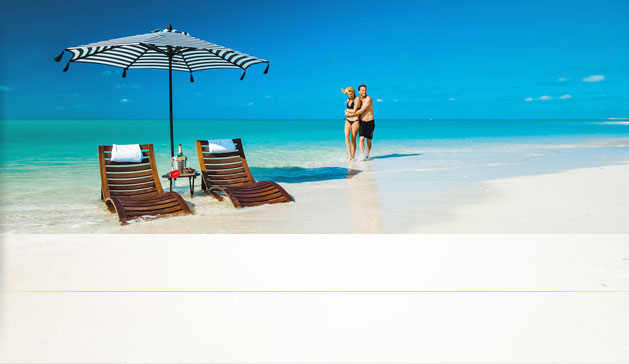 A Playful Couple Standing In The Crystal Blue Ocean Next To Their Loung Chairs At An All Inclusive Sandals Resort