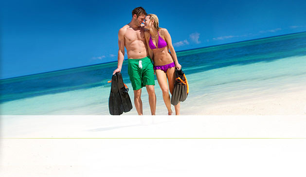 A Couple In Love, Ready For Activities Like Snorkeling At The Beautiful White Beach Of An All Inclusive Sandals Resort.